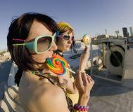 Fun girls on the roof with lollipops Royalty Free Stock Photos