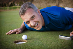 Fun on the Golf Course. Get in the hole, Please! A 40-something male golfer laughs at how close he came to making the putt Stock Photos