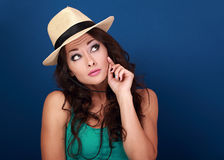 Fun grimacing frightened woman in hat thinking and looking up on Stock Photography