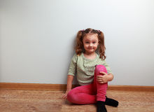 Fun grimacing girl sitting on the floor and smiling Stock Image
