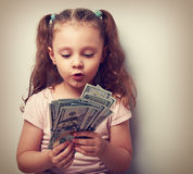 Fun grimacing kid girl looking and counting money in the hands. Vintage closeup portrait Stock Photography