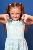 Fun grimacing kid girl showing thumb down on blue background. Cl Stock Image