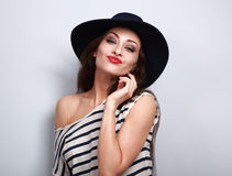 Fun grimacing young woman in hat with red lipstick on blue backg Stock Image