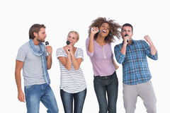 Fun group singing at karaoke. On white background Stock Image