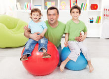 Fun with gymnastic balls. Young boys playing with their father Royalty Free Stock Photo
