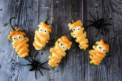 Halloween mummy jalapeno poppers, top view on old wood. Fun Halloween mummy jalapeno poppers, top view on rustic old wood background royalty free stock images