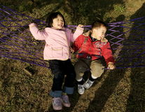 Fun with hammock. A candid picture of a little chinese girl and boy playing hammock and enjoying sunshine Stock Photography