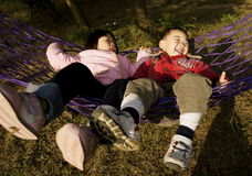 Fun with hammock. A candid picture of a chinese little girl and boy laughing and basking in a hammock Royalty Free Stock Photos