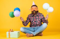 Fun and happiness concept. happy man holding colorful helium balloons. hipster smiling happily. having fun on party