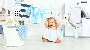Fun happy baby boy  to wash clothes and laughs in laundry Stock Images