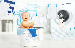 Fun happy baby boy  to wash clothes and laughs in laundry Royalty Free Stock Images