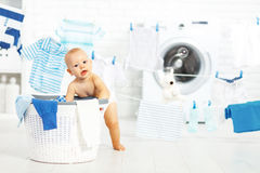 Fun happy baby boy  to wash clothes and laughs in laundry Stock Photography
