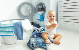 Fun happy baby boy  to wash clothes and laughs in laundry Stock Photos