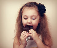 Fun happy kid girl eating dark chocalate. Closeup Vintage Royalty Free Stock Image