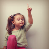 Fun happy kid girl showing the finger up on empty space. Vintage Royalty Free Stock Photos