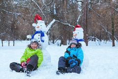 Fun, happy kids playing with snowman. In Winter park, outdoor Stock Photos