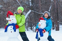Fun, happy kids playing with snowman. In Winter park, outdoor Stock Photography