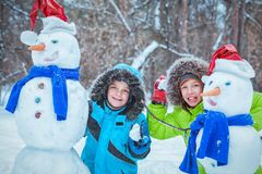 Fun, happy kids playing with snowman. In Winter park, outdoor Royalty Free Stock Photo