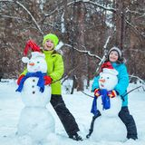 Fun, happy kids playing with snowman. In Winter park, outdoor Royalty Free Stock Photography