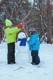 Fun, happy kids playing with snowman in Winter park. Outdoor, walk in forest Stock Image