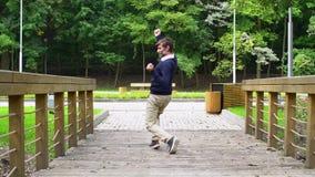 Fun happy middle age man with beard dancing on bridge in park stock video