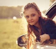 Fun happy traveling kid girl looking from the car window on summ Royalty Free Stock Photos