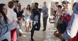 Fun happy young African businessman doing silly winner dance celebrating success with colleagues at workplace party. stock video footage
