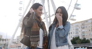 Fun happy young women in front of a ferris wheel. Fun happy young women standing together in front of a ferris wheel smiling at the camera  high key background stock video