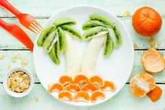 Fun and healthy fruit salad for kids, kiwi banana mandarin palms. Fun and healthy fruit salad for kids, kiwi banana mandarin palm trees Royalty Free Stock Photo