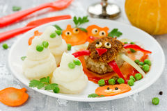 Fun and healthy idea for kids lunch or dinner on Halloween meal. Meat cutlet in the form of a spider, mashed potatoes ghosts and colorful vegetable garnish on Royalty Free Stock Photo