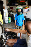 Fun helmet boy. Portrait of young boy playing with fathers motorbike helmet and helping his dad with fixing a motorcycle in the garage Stock Images