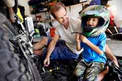 Fun helmet boy. Portrait of young boy playing with fathers motorbike helmet and helping his dad with fixing a motorcycle in the garage Royalty Free Stock Image