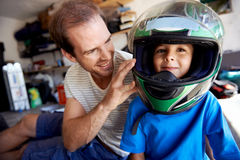 Fun helmet boy. Portrait of young boy playing with fathers motorbike helmet and helping his dad with fixing a motorcycle in the garage Royalty Free Stock Images
