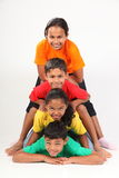 Fun human totem pole by four young school friends Stock Photos
