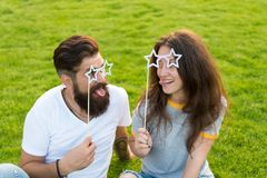 Fun ideas. Funny couple in love relaxing on green grass. Happy couple having fun with prop glasses on sticks. Sensual stock images