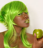 Green Apple Girl. A fun image of a woman with a green apple and matching wig and makeup Stock Image