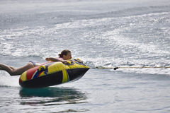 Fun on inner tube. Young woman laying on inner tube being pulled by boat Stock Photography