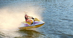 Fun on jet ski. Adult having fun jumping a wave riding yellow and white Sea Doo jet ski in California Ocean Stock Image