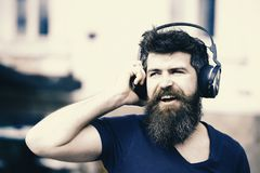 Fun, joy and music concept. Bearded hipster man wearing big earphones listening to music. Young man singing along to his. Favorite song while walking in city royalty free stock photography
