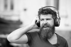 Fun, joy and music concept. Bearded hipster man wearing big earphones listening to music. Young man singing along to his. Favorite song while walking in city Royalty Free Stock Images