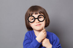 Fun kid eyeglasses concept for imaginative preschool child. Fun kid glasses concept - imaginative preschool child holding fake black round eyeglasses for playing stock photo
