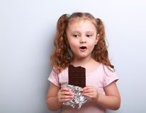 Fun kid girl eating dark chocolate and amazing how it tasty Stock Photography