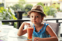 Fun kid girl in fashion hat drinking smoothie juice in street re. Staurant royalty free stock photo