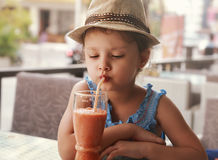 Fun kid girl in hat drinking smoothie juice from glass in street Stock Photos