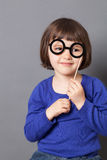 Fun kid glasses concept for eyesight. Fun kid glasses concept - smiling preschool child holding fake black round eyeglasses for playing like adult or dressing up royalty free stock photos