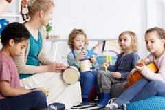 Fun in kindergarten. Four preschoolers having fun in kindergarten playing the instruments stock photography