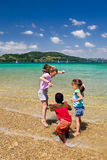 Fun in at the Lake. Three small children jumping up and down in the crystal clear water of the Lac du Paladu in France Royalty Free Stock Photos