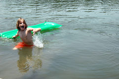 Fun in Lake. A boy smiling and splashing in lake with a raft royalty free stock photography