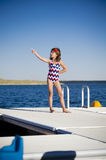 Fun at the lake dock. Young girl with swimming suite standing on dock pointing , smiling by lake on a summer day Stock Images