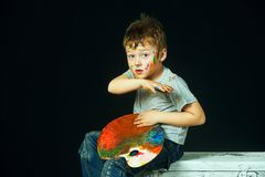 A fun little artist covered in paint. Boy with smeared hands in paint on a dark background . Cheerful artist royalty free stock images